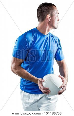 Rugby player looking away while holding ball aside against white background
