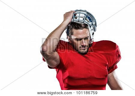 American football player in red jersey removing helmet against white background