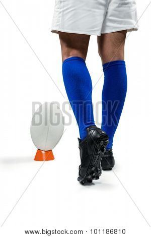 Low section of rugby player going to kick the ball against white background