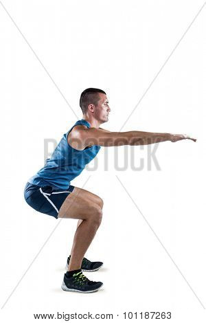Full length of fit man doing squats on white background