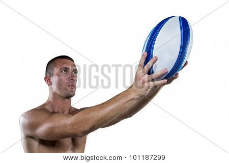Shirtless rugby player holding ball against white background