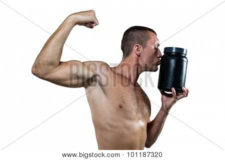 Shirtless athlete flexing muscles while kissing nutritional supplement container against white baackground