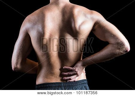 Rear view of shirtless man with back pain against black background