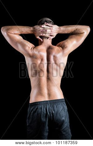 Rear view of shirtless muscular crossfiter standing over black background