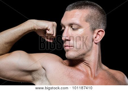 Close-up serious shirtless athlete flexing muscles against black background