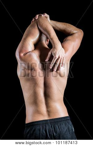 Rear view of shirtless man stretching elbow against black background