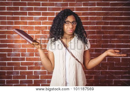 Student shrugging her shoulders n red brick background