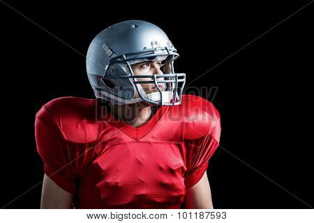 American football player looking away while standing against black background