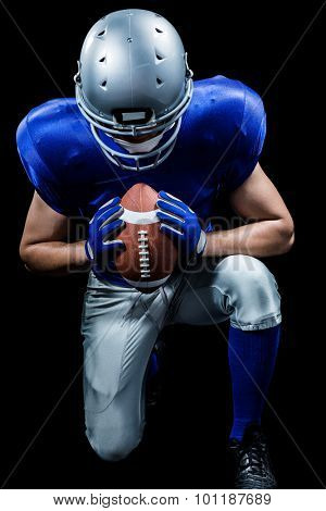 American football player kneeling while holding ball against black background