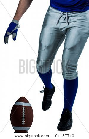 Low section of American football player kicking ball over white background