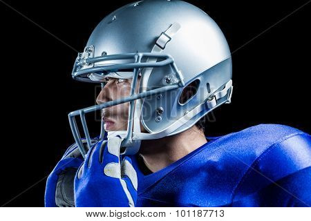 Sportsman wearing helmet looking away against black background