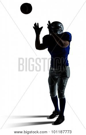 American football player catching ball against white background