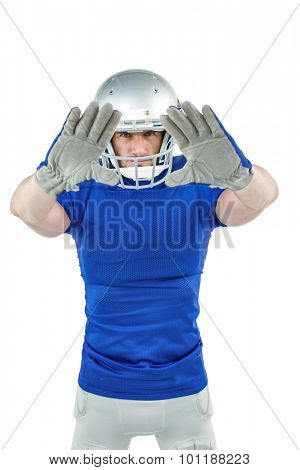 Portrait confident American football player defending against white background