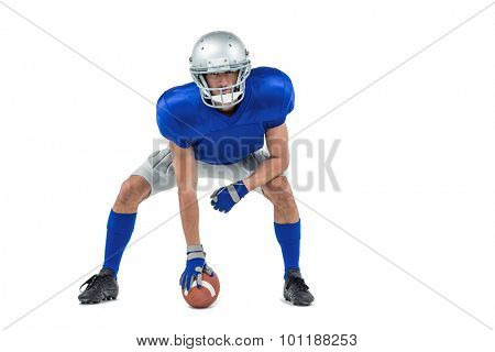 Portrait of alert American football player in attack stance against white background