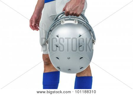 Midsection of American football player handing his helmet on a white background