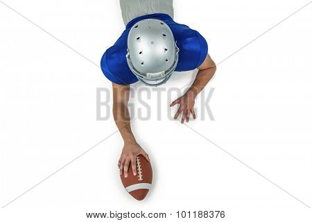 Rear view of American football player lying in front with ball against white background