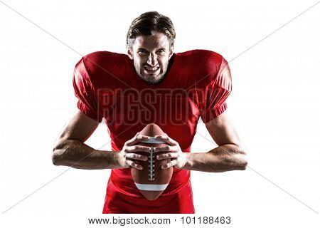 Portrait of aggressive American football player in red jersey holding ball on white background