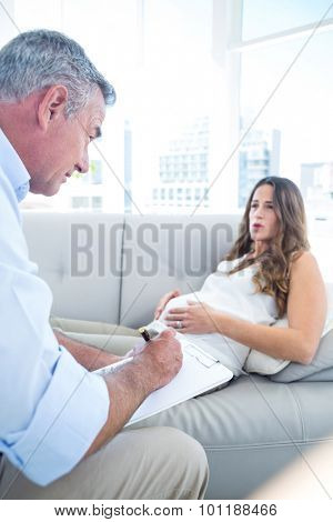 Preganant woman talking with psychiatrist while relaxing at home