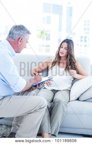 Psychiatrist advising preganant woman while sitting on sofa at home