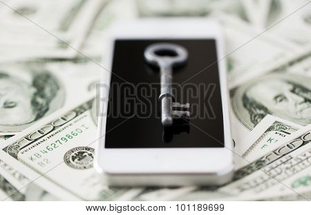business, finance, technology and security concept - close up of smartphone with black blank screen, key and dollar money