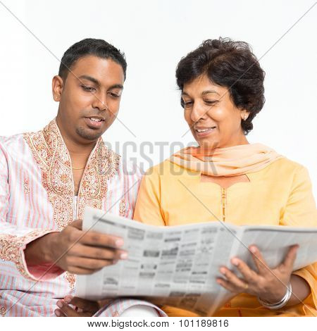 Portrait of Indian family reading newspaper together at home. Mature 50s Indian mother and 30s grown son.