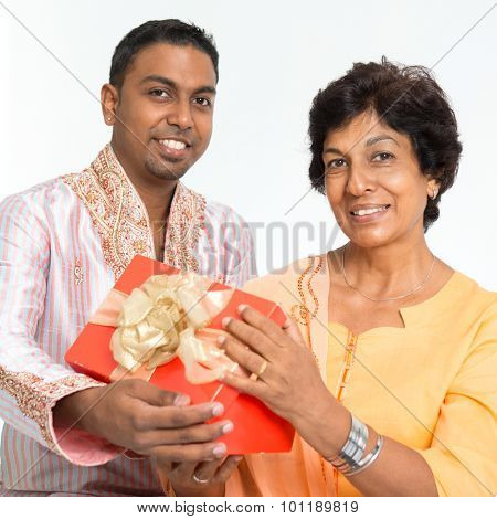 Portrait of happy Indian family celebrate mothers day at home. Mature 50s Indian mother received surprised gift from her 30s grown son.