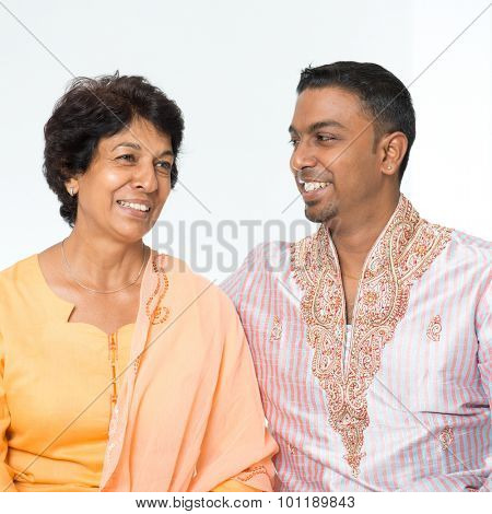 Portrait of happy Indian family communicating at home. Mature 50s Indian mother and her 30s grown son.