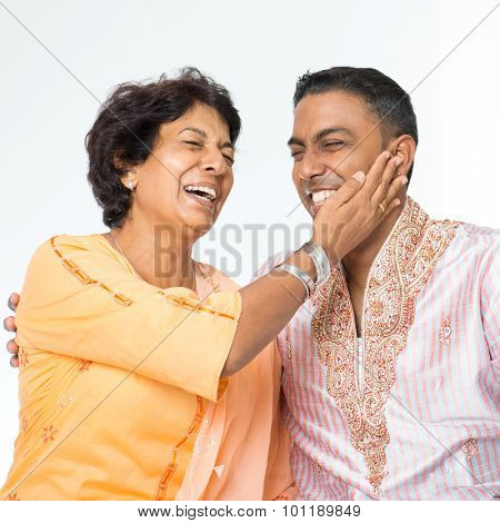 Portrait of happy Indian family having fun conversation at home. Mature 50s Indian mother and her 30s grown son.