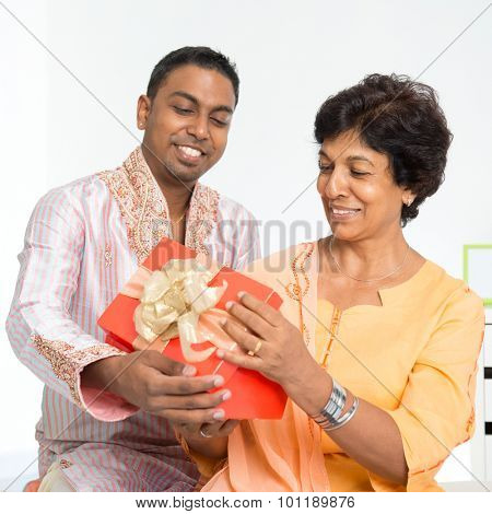 Portrait of happy Indian family celebrate birthday at home. Mature 50s Indian mother received surprised present from her 30s grown son.