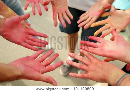 Hands of young people with Indian dyes on Holi color festival