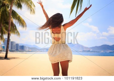 Slim Girl In White Backside View Poses With Hands Up On Beach