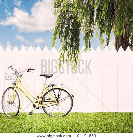 yellow bike in front of a white fence