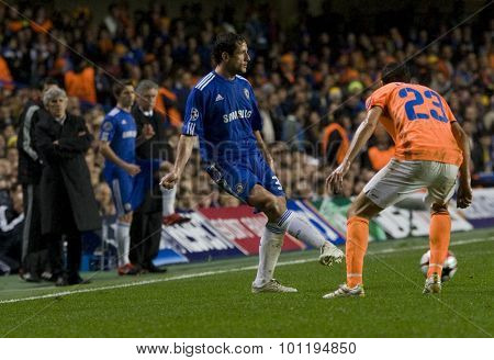 LONDON, ENGLAND. 08 December 2009. - Juliano Belletti playing for Chelsea plays a pass as Helio Pinto playing for APOEL FC  watches during the Uefa Champions League match