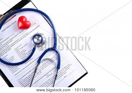 Stethoscope with medical history and decorative heart isolated on white