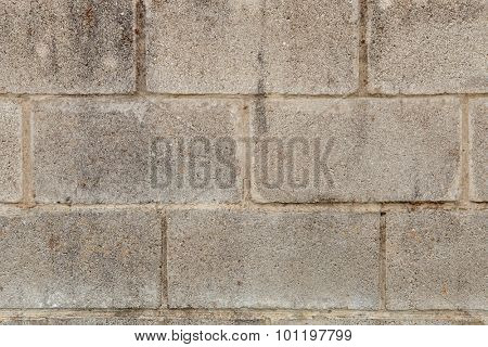 Grey wall of cement blocks damaged by the passage of time