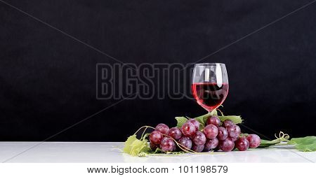Bunch of red grapes with leaves and red wine glass