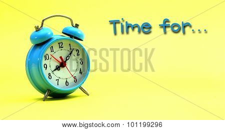 Picture of blue alarm clock on a yellow background