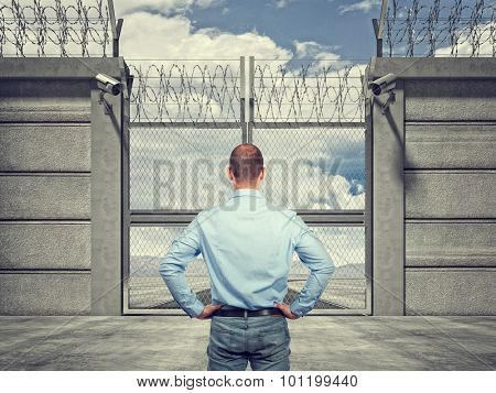 3d image of security border line gate with razor wire and man