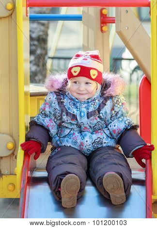 Smiling toddler girl wearing warm autumn clothes with childish bobble long hat sitting on playground