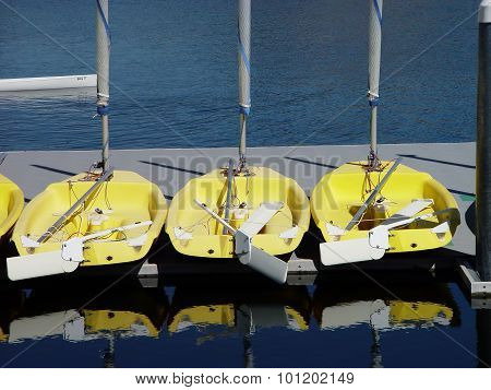 Small Yellow Sail Boats Sitting On Dock