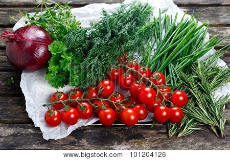 Fresh Tomatoes And Green Vegetables. Onion, Dill, Rosemary, Parsley, Chives And Thyme. On Old Wooden