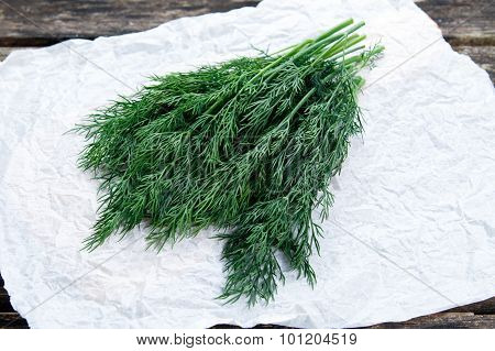 Fresh Green Vegetables Bunch Of Dill On Crumpled Paper And Old Wooden Table.