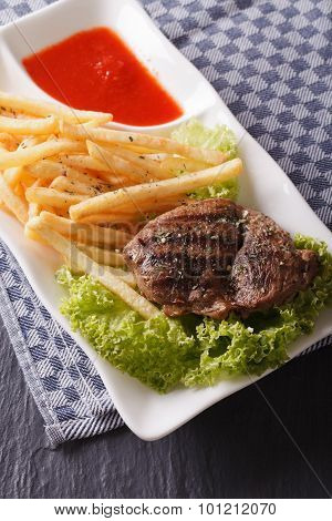 Grilled Beefsteak With French Fries And Lettuce On The Plate. Vertical