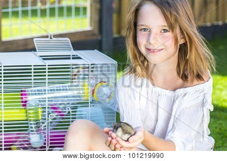Girl sitting in the backyard with a small hamster in palms