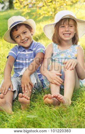 Playful kids sit on summer grass