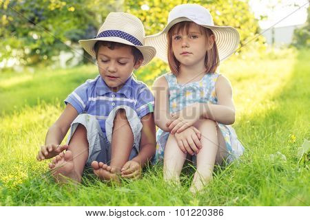 Two kids in hats sitting in park on grass