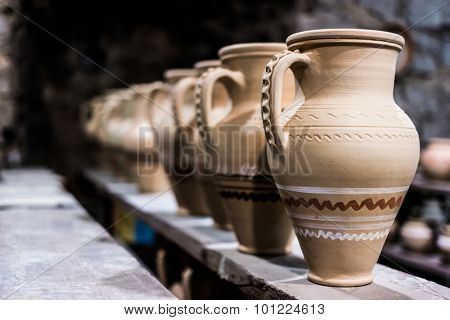 decorated clay pots on shop shelf