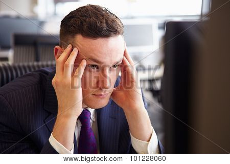 Head and shoulders of a young stressed businessman, head in hands