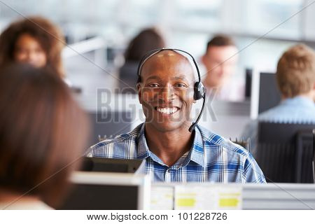 African American man working in call centre, looks to camera