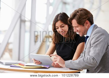 Two corporate business colleagues working together in office